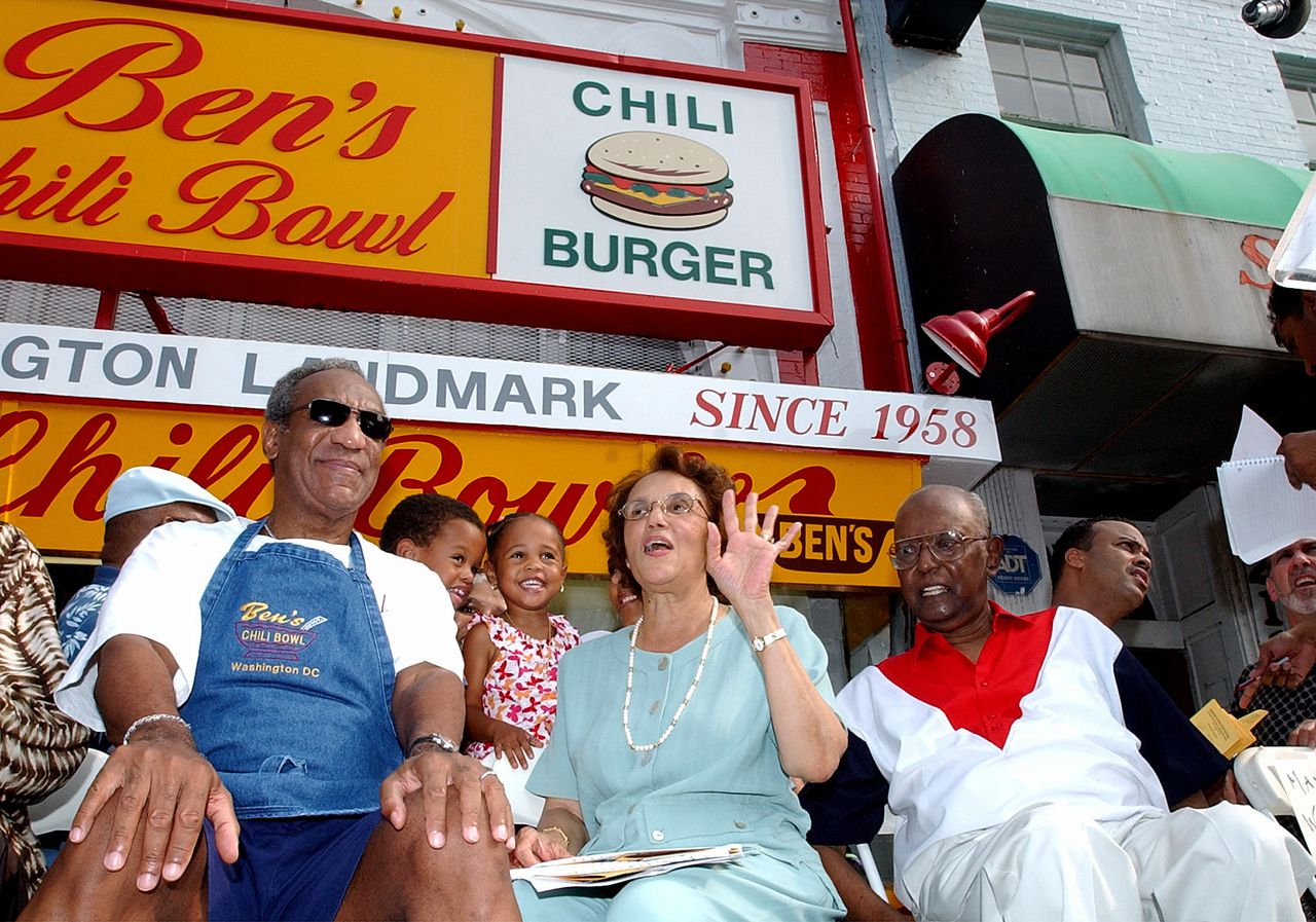 Comedian Bill Cosby, left, joins Ben Ali, right, and Ali's wife, Virginia during a celebration on the 45th anniversary of Ben's Chili Bowl Restaurant in Washington Friday, Aug. 22, 2003. Ben's opened in the Shaw neighborhood in 1958 winning over the community and becaming one of the few businesses in the area to remain open during the riots of the 1960s, and the high crime of the 1970's and early 80's. (AP Photo/Dennis Cook)