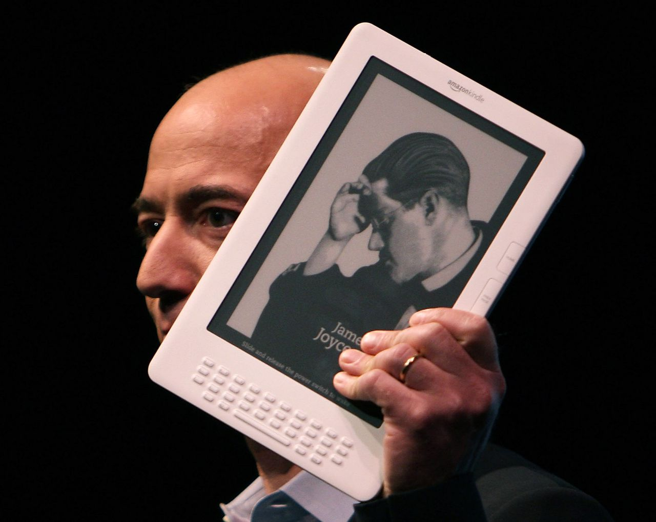 Nieuwe Kindle is beter voor kranten New York, 7 mei. Bestuursvoorzitter Jeff Bezos van Amazon toonde gisteren een nieuwe versie van de e-reader Kindle bij een presentatie samen met The New York Times. Met een scherm van 9,7 inch is het apparaat groter dan de huidige versie (6 inch), en daarmee geschikter voor kranten. Onder meer The New York Times, The Washington Post en The Boston Globe geven lezers korting op het apparaat, dat in de winkel 489 dollar (367 euro) moet kosten. De mobiele internetverbinding werkt alleen nog in de VS. Foto AFP NEW YORK - MAY 06: Amazon CEO Jeff Bezos holds the new Kindle DX, which he unveiled at a press conference at the Michael Schimmel Center for the Arts at Pace University May 6, 2009 in New York City. Bezos was joined by Arthur Sulzberger, Jr., publisher of The New York Times and chairman of The New York Times Company. The Kindle DX, a new purpose-built reading device, features a larger 9.7-inch electronic paper display, built-in PDF reader, auto-rotate capability, and storage for up to 3,500 books. Amazon has also partnered with select major newspapers to offer readers discounts on the DX in return for long-term subscriptions. The Kindle DX is available for pre-order starting today for $489.00 USD and will ship this summer. Spencer Platt/Getty Images/AFP == FOR NEWSPAPERS, INTERNET, TELCOS & TELEVISION USE ONLY ==