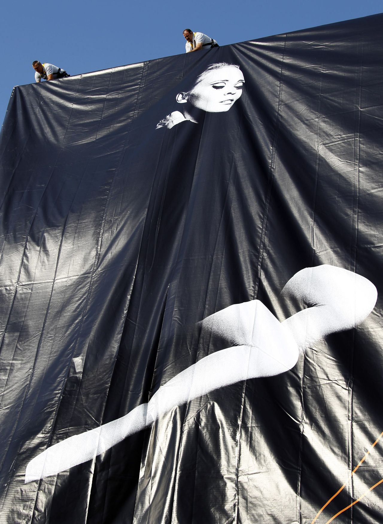 Workers set up a giant canvas of the official poster of the 64th Cannes Film Festival showing U.S. actress Faye Dunaway, on the facade of the Festival Palace in Cannes May 9, 2011. The Cannes Film Festival runs from May 11 to 22. REUTERS/Eric Gaillard (FRANCE - Tags: ENTERTAINMENT)