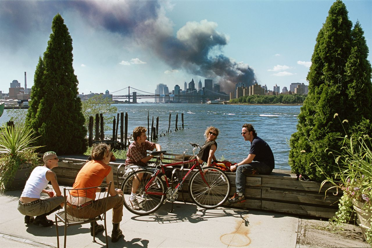 USA. Brooklyn, New York. September 11, 2001. Young people relax during their lunch break along the East River while a huge plume of smoke rises from Lower Manhattan after the attack on the World Trade Center. Contact email: New York : photography@magnumphotos.com Paris : magnum@magnumphotos.fr London : magnum@magnumphotos.co.uk Tokyo : tokyo@magnumphotos.co.jp Contact phones: New York : +1 212 929 6000 Paris: + 33 1 53 42 50 00 London: + 44 20 7490 1771 Tokyo: + 81 3 3219 0771 Image URL: http://www.magnumphotos.com/Archive/C.aspx?VP3=ViewBox_VPage&IID=2K7O3RK0762&CT=Image&IT=ZoomImage01_VForm