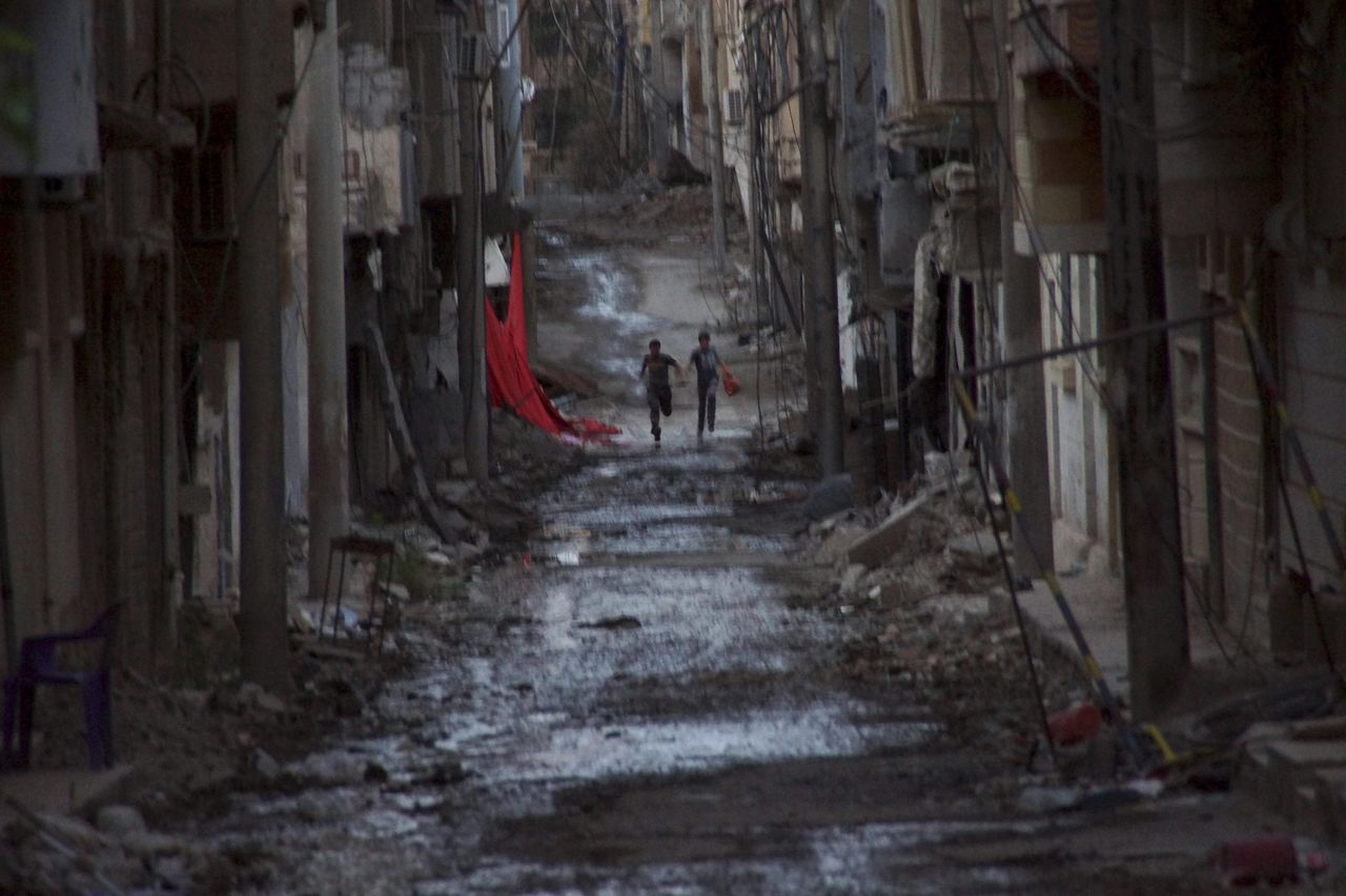 People run down a street in Deir al-Zor, May 18, 2013. Picture taken May 18, 2013. REUTERS/Khalil Ashawi (SYRIA - Tags: POLITICS CIVIL UNREST CONFLICT TPX IMAGES OF THE DAY)