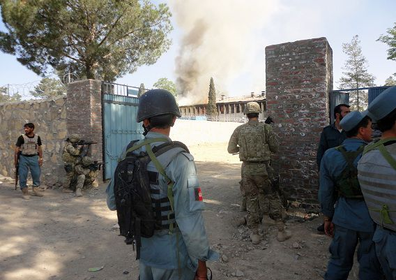"""Afghan policemen and NATO troopers exchange fire with insurgent attackers as smoke rises from the Afghan traffic police headquarters in Khost province on May 22, 2011. Three police officers were killed on May 22 after suicide attackers armed with machine guns stormed a traffic police headquarters in eastern Afghanistan, the provincial police chief told AFP. """"Three traffic police officers have been killed so far, one policeman and one civilian are wounded and the fighting is still ongoing,"""" Abdul Hakim Ishaqzai, Khost provincial police chief, told AFP. AFP PHOTO/Rasool Adil"""