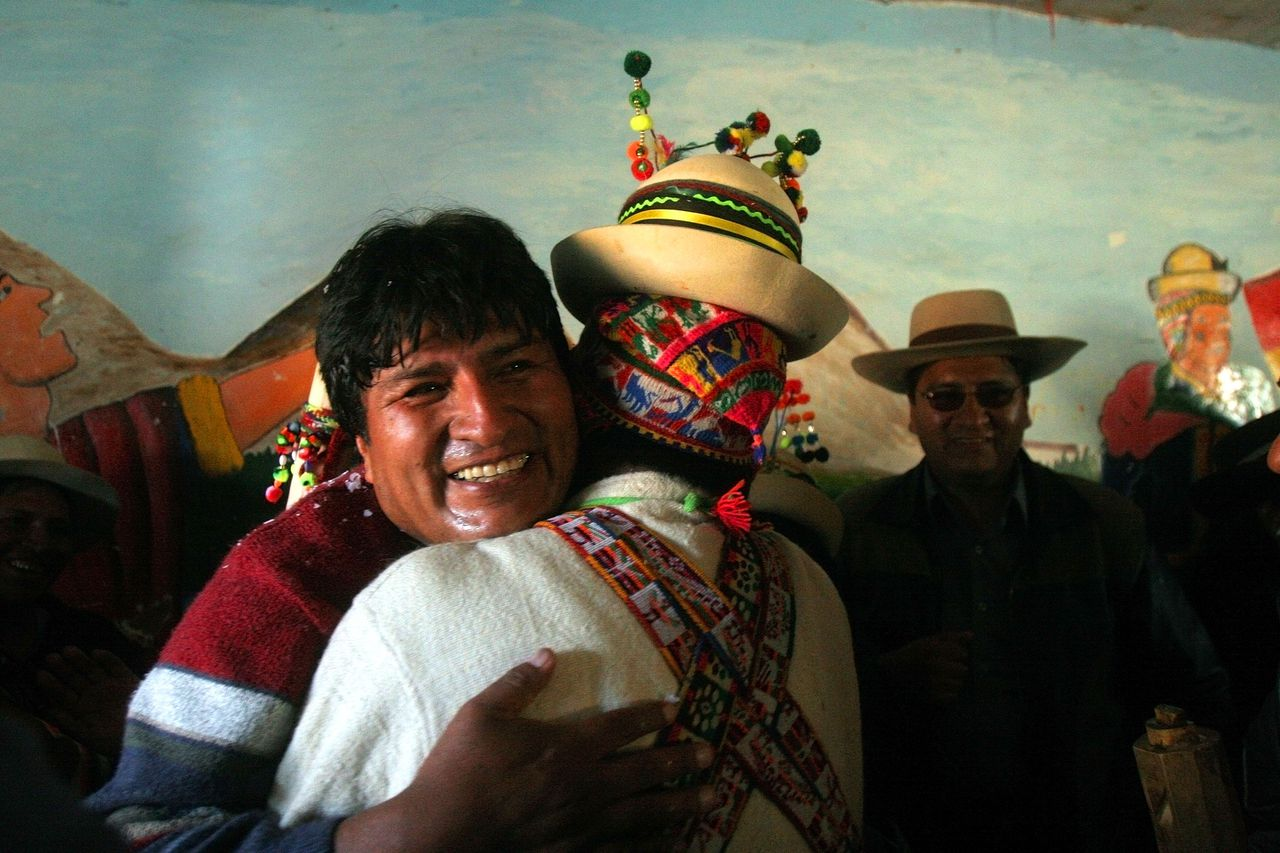 President Morales omhelst een indiaanse vrouw in zijn thuisdorp. (Foto AP) Bolivian President Evo Morales smiles and embraces one of the several relatives from his hometown Orinoca, some 297 kilometers (185 miles) south of La Paz, Bolivia on Saturday, July 22, 2006. A stoutly built indigenous Aymara who was raised in severe poverty and rose to power as a scrappy agitator for Bolivia's coca growers, Morales is unusually approachable for his constituents, but avoids the lifestyle of the European-descended elites who long ruled South America's poorest country.The populist upheaval he's leading on behalf of Bolivia's long-marginalized indigenous majority has Morales riding at 80 percent popularity, the highest in Latin America. (AP Photo/Dado Galdieri)