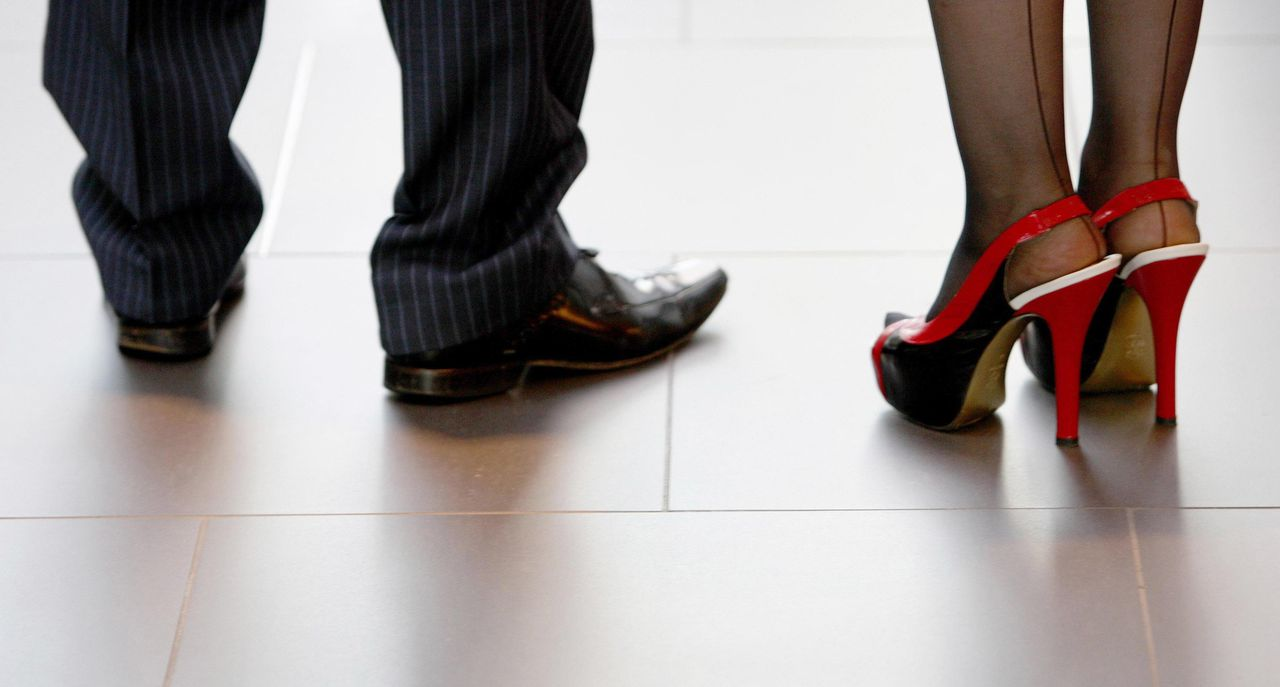 """File photo dated 15/09/09 of the shoes of a man and a woman. Most women believe a """"glass ceiling"""" still exists in business, holding back their chances of being promoted to senior management or serving on company boards, according to a new study by the Institute of Leadership & Management (ILM)."""