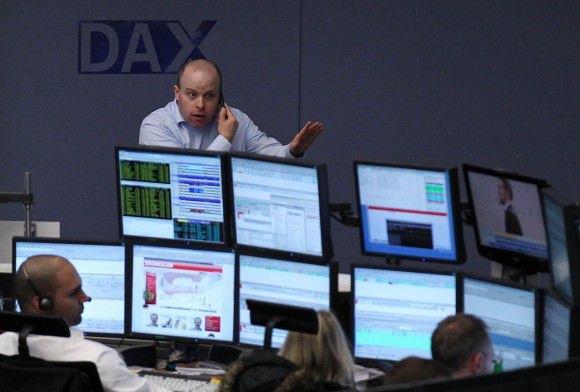 A trader reacts in front of a DAX logo at the Frankfurt stock exchange November 11, 2011. REUTERS/Alex Domanski (GERMANY - Tags: BUSINESS)