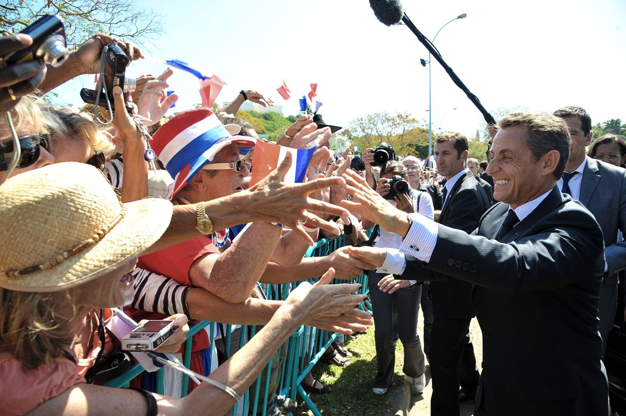 French President Nicolas Sarkozy shakes hands on August 26, 2011 as he arrives in Noumea on the eve of the opening ceremony of the Pacific Games. Nicolas Sarkozy called for rival groups in New Caledonia to show restraint after recent deadly protests in the South Pacific archipelago, as he began his visit as French president in the French territory, which is going through a process of de-colonisation. AFP PHOTO MARC LE CHELARD