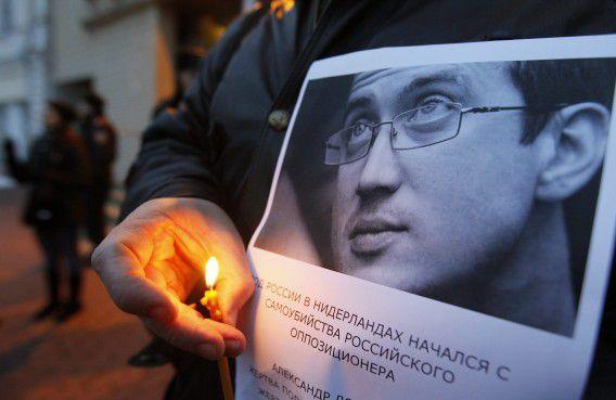 Een vriend van Aleksandr Dolmatov en een groep activisten herdenken de dood van de Russische asielzoeker, vorige week voor de deur van de Nederlandse ambassade in Kiev.