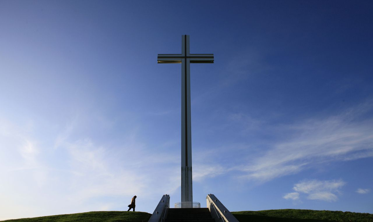 """(FILES) A picture taken on November 26, 2009 shows a man walking past the Papal Cross, which was built for the visit of the late Pope John Paul II in September 1979, in Phoenix Park, in Dublin. Ireland said late on November 3, 2011 it would close its embassy to the Vatican as part of a shake-up of its missions abroad following a row with the Holy See earlier this year over a child sex abuse scandal. """"It is with the greatest regret and reluctance that the government has decided to close Ireland's (embassy) to the Holy See,"""" said a statement from the foreign ministry. AFP PHOTO/Peter Muhly"""
