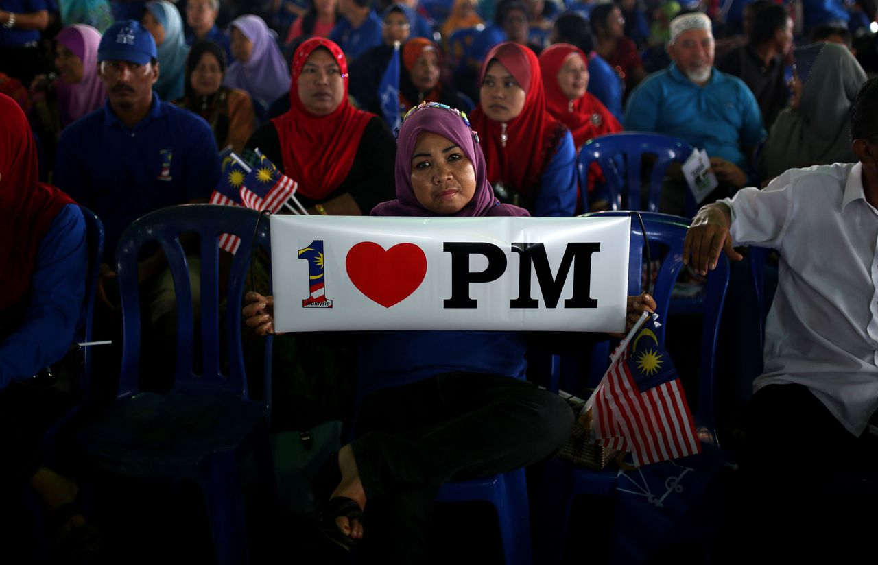 TOPSHOTS A supporter displays a placard as Malaysia's premier Najib Razak, president of the ruling party National Front, speaks during his party's campaign event in Kuala Kangsar northen Perak on April 26, 2013. Opposition leader Anwar Ibrahim held a slight edge in support over Malaysian premier Najib Razak, according to a survey released ahead of a hotly anticipated election showdown on May 5. AFP PHOTO / MOHD RASFAN