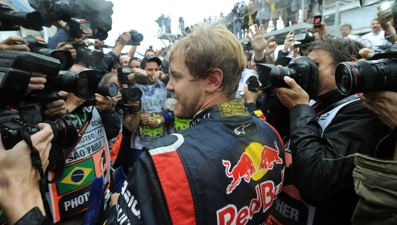 German Formula One driver Sebastian Vettel is surrounded by photographers as he celebrates his F-1 World Championship on November 25, 2012 after arriving 6th in the Brazil F-1 GP at the Interlagos racetrack in Sao Paulo, Brazil. AFP PHOTO/ANTONIO SCORZA