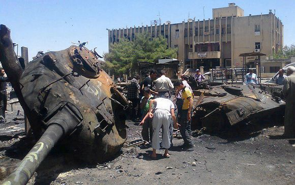 Caption: In this citizen journalism image provided by Edlib News Network ENN, anti-Syrian regime citizens look at a Syrian tank that was damaged during clashes between rebels and Syrian government forces, at the northern town of Ariha , in Idlib province, Syria, Monday, June 4, 2012. European leaders are expected to press the contentious issue of Syria at a European Union-Russian summit Monday in St. Petersburg, but few believe Russian President Vladimir Putin will agree to ramp up pressure on the Syrian government. (AP Photo/Edlib News Network ENN) THE ASSOCIATED PRESS IS UNABLE TO INDEPENDENTLY VERIFY THE AUTHENTICITY, CONTENT, LOCATION OR DATE OF THIS HANDOUT PHOTO