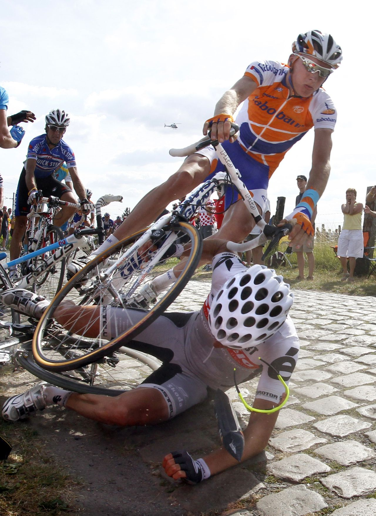 Riders fall on the cobblestones during the third stage of the Tour de France cycling race between Wanze and Arenberg-Porte Du Hainaut, July 6, 2010. REUTERS/Eric Gaillard (FRANCE - Tags: SPORT CYCLING)