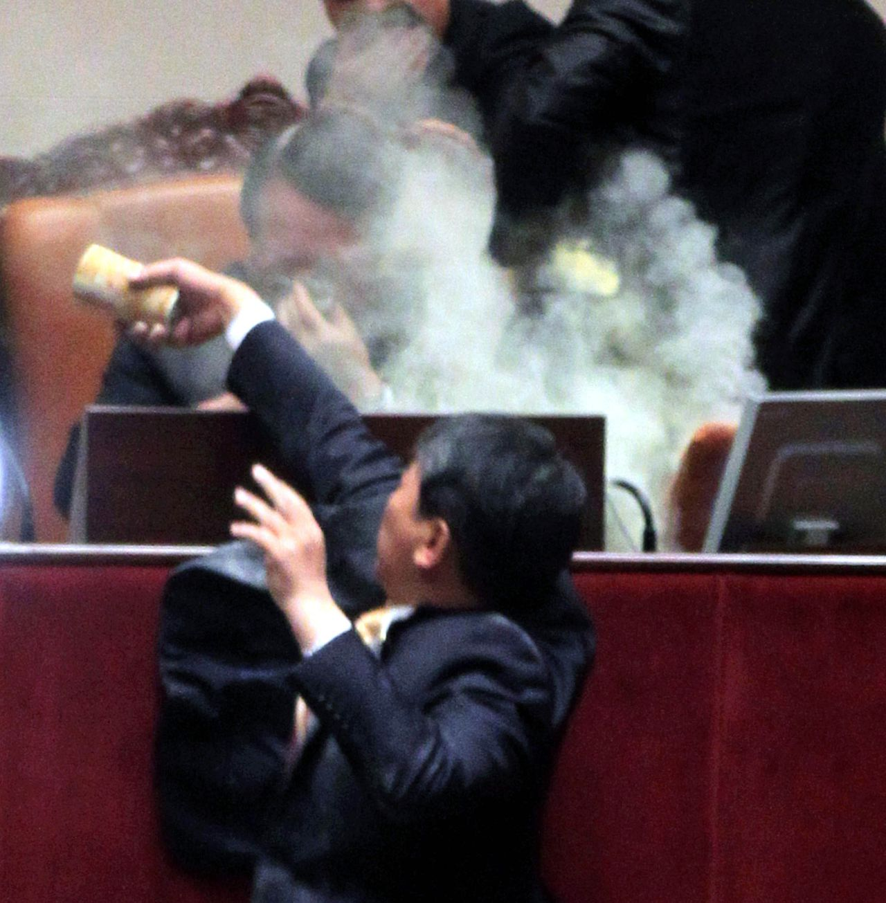 South Korean lawmaker Kim Sun-Dong (bottom) of the Democratic Labour Party detonates a tear gas canister towards the chairman's seat at the National Assembly in Seoul to try to stop the ruling Grand National Party's move to ratify a bill on a free trade agreement with the United States on November 22, 2011. South Korea's parliament approved a free trade agreement with the United States in a chaotic session, minutes after the opposition legislator set off a tear gas canister in protest at the pact. REPUBLIC OF KOREA OUT AFP PHOTO / NOCUT NEWS