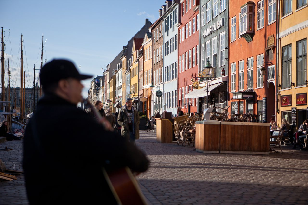 A musician plays a guitar on the street outside bars in the Nyhavn district of Copenhagen, Denmark, on Tuesday, March 13, 2012. Denmark's $460 billion mortgage bond system is too reliant on quarterly auctions to refinance about two thirds of its debt, and needs to do more to distribute the risk over the whole year, the central bank warned. Photographer: Ulrik Jantzen/Bloomberg via Getty Images