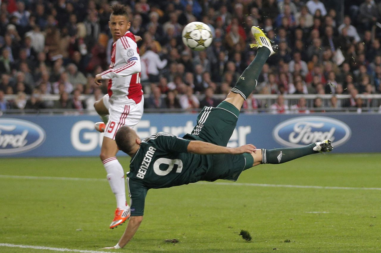 Real Madrid player Karim Benzema scores with a bicycle kick before Ajax player Tobias Sana, left, can stop him during the Champions League Group D soccer match at ArenA stadium in Amsterdam, Netherlands, Wednesday Oct. 3, 2012. This goal brings the score to 2-0. (AP Photo/Peter Dejong)