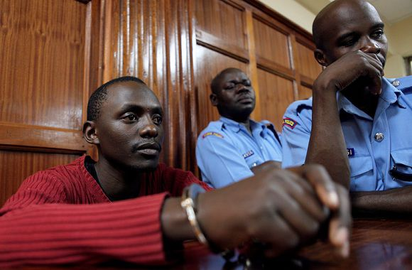 Caption: Elgiva Bwire Oliacha (L), also known as Mohamed Seif, who was arrested on Tuesday at his Kayole residence with a cache of hand grenades and guns, appears at the chief magistrates court in capital Nairobi October 26, 2011. Oliacha pleaded guilty on Wednesday to causing grievous harm to people at a bus station in the capital Nairobi two days ago and being a member of the Somali rebel group al Shabaab. REUTERS/Noor Khamis (KENYA - Tags: CRIME LAW CIVIL UNREST)